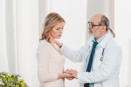 side view of senior doctor cheering up upset patient in clinic