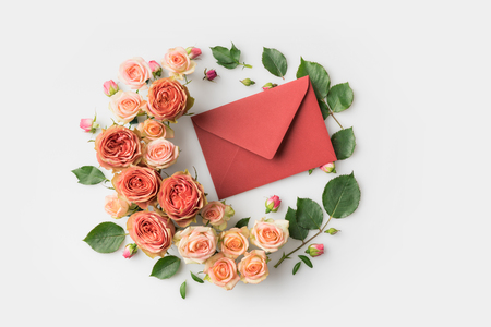 envelope surrounded by beautiful pink flowers isolated on white