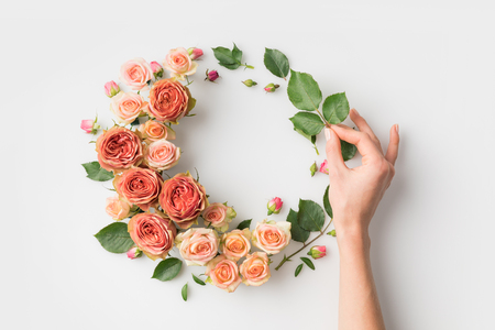 hand with pink flower wreath isolated on white