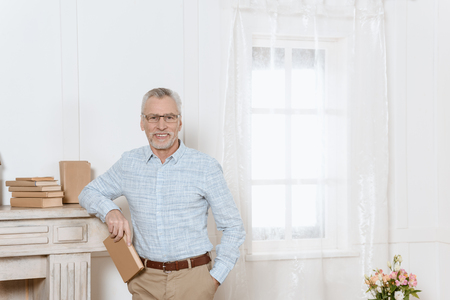 Senior man stands by fireplace in room holding a book