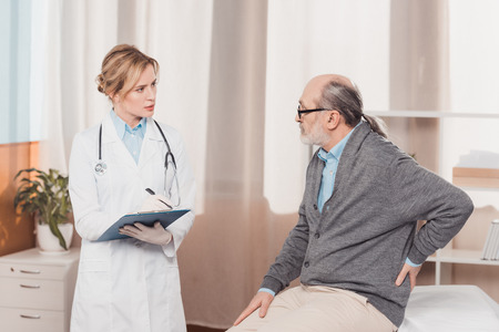doctor in white coat with notepad listening to patients complaint in clinic