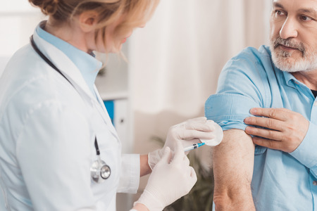 doctor in white coat making injection to senior patient in clinic Imagens - 114777736