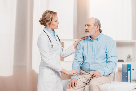 portrait of doctor in white coat cheering up senior patient in clinic