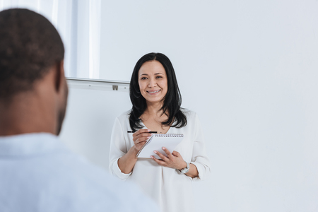 smiling female psychoanalyst taking notes while standing at whiteboard in office Stock Photo - 114777761