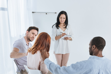 psychotherapist taking notes while anonymous group supporting depressed woman Stock Photo - 114777765