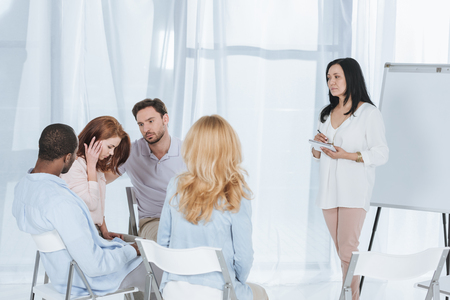 middle aged multiethnic people supporting each other while psychotherapist taking notes during group therapy Stock Photo - 114777768