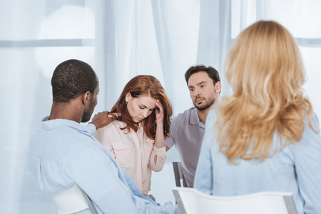 multiethnic middle aged people supporting depressed woman during anonymous group therapy