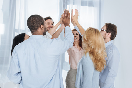 happy multiethnic middle aged people giving high five during group therapy Stock Photo