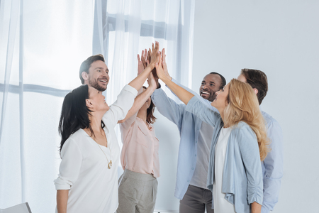 cheerful multiethnic mature people giving high five during group therapy Stock Photo - 114777778