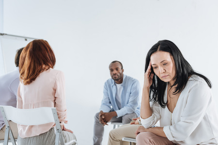 depressed asian woman looking down and multiethnic group sitting behind