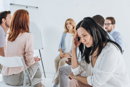 close-up view of upset asian middle aged woman and people sitting on chairs behind during group therapy