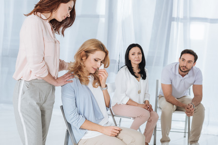middle aged people supporting depressed woman during anonymous group therapy