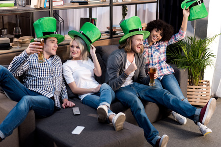 happy multiethnic friends celebrating saint patrick day at home