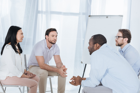 multiethnic middle aged people sitting on chairs during anonymous group therapy Stock Photo