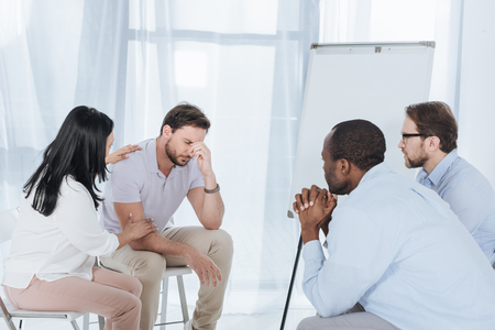 multiethnic middle aged people sitting on chairs and supporting upset man during anonymous group therapy