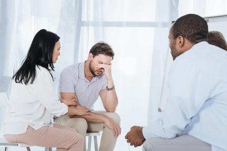 multiethnic mid adult people supporting depressed man during anonymous group therapy Stock Photo
