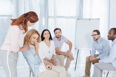 psychotherapist supporting middle aged woman during group therapy Stock Photo