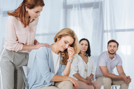 middle aged people supporting crying woman during anonymous group therapy Stock Photo