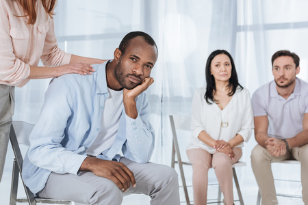 cropped shor of middle aged people supporting depressed african american man during anonymous group therapy