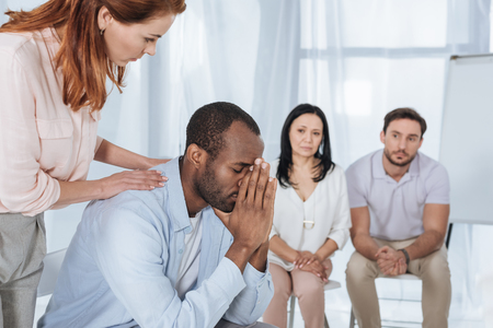 middle aged people supporting upset african american man during anonymous group therapy Stock Photo - 114777806