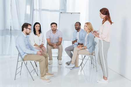 psychotherapist writing in notebook and talking with multiethnic people sitting on chairs during group therapy