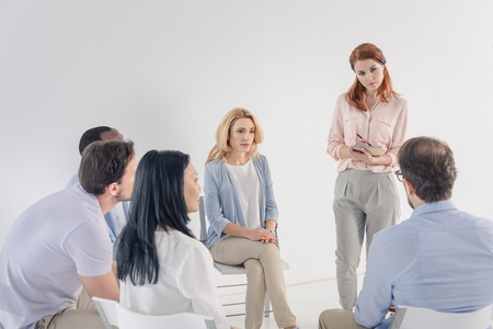 psychotherapist taking notes and working with mature multiethnic people during group therapy Stock Photo - 114777808