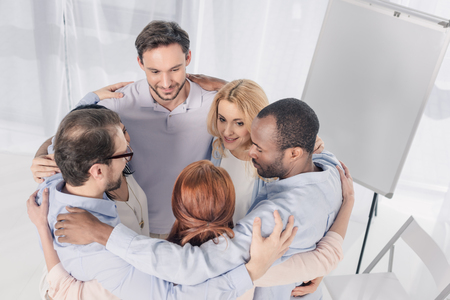 mature multiethnic people standing in circle and embracing during group therapy Stock Photo - 114777810