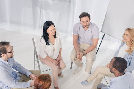 high angle view of smiling multiethnic middle aged people sitting on chairs and talking during group therapy Stock Photo - 114777813