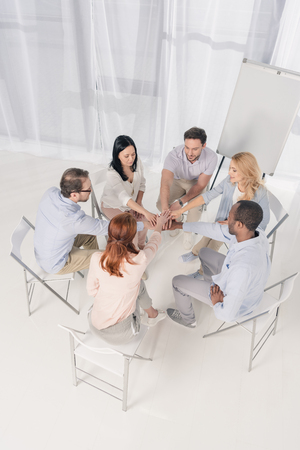 high angle view of multiethnic middle aged people sitting on chairs and stacking hands during group therapy