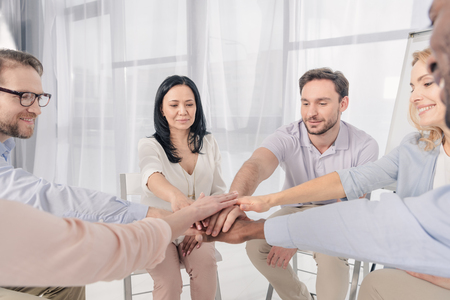 cropped shot of multiethnic middle aged people stacking hands during group therapy