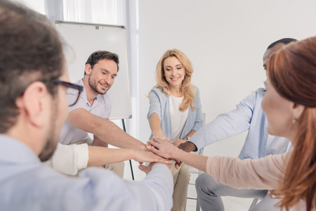 selective focus of middle aged multiethnic people stacking hands during group therapy Stock Photo - 114777821