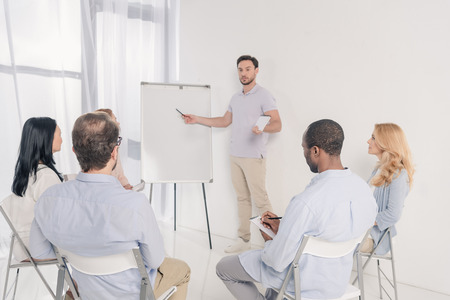 male psychotherapist pointing at blank whiteboard and multiethnic group of people sitting on chairs during therapy Stock Photo - 114777829