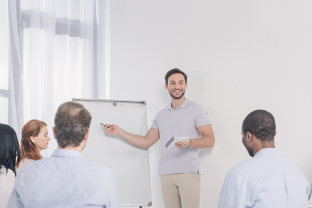 smiling man holding notebook and pointing at blank whiteboard while looking at multiethnic people during group therapy Stock Photo - 114777832
