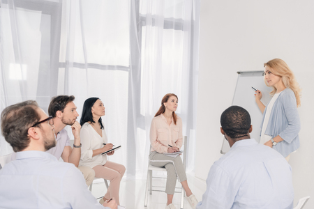 female psychotherapist pointing at blank whiteboard and multiethnic group sitting on chairs during therapy Stock Photo