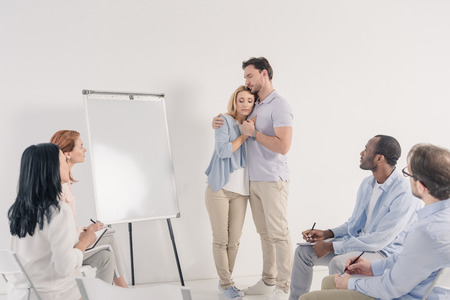 middle aged couple holding hands while standing near blank whiteboard and other people sitting on chairs during group therapy