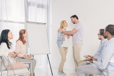 mature couple looking at each other while standing near blank whiteboard and other people sitting on chairs during group therapy