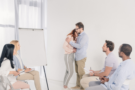 mature couple hugging while standing near blank whiteboard and other people sitting on chairs during group therapy Stock Photo - 114777885