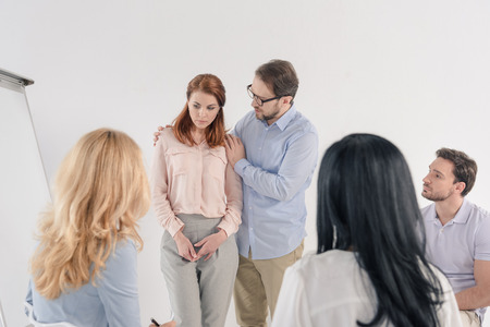 psychotherapist supporting upset woman during group therapy