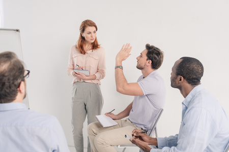 cropped shot of middle aged multiethnic people talking together during anonymous group therapy Stock Photo - 114777887