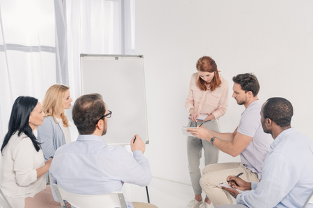psychotherapist standing near whiteboard and talking with multiethnic people during group therapy Stock Photo