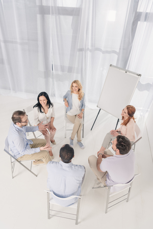 high angle view of middle aged people sitting on chairs and talking during group therapy Stock Photo