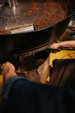 partial view of coffee roaster working on roasting machine Archivio Fotografico