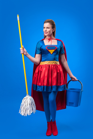attractive woman in superhero costume with mop and bucket for cleaning isolated on blue Фото со стока