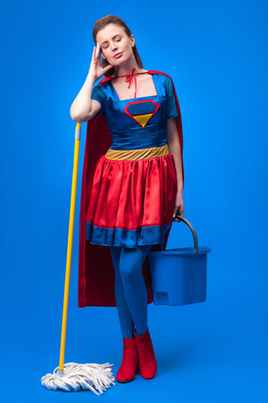 tired woman in superhero costume with mop and bucket for cleaning isolated on blue Stock Photo