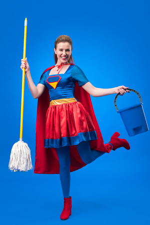 happy woman in superhero costume with mop and bucket for cleaning isolated on blue Stock Photo