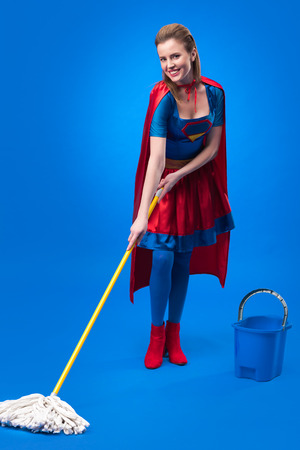 cheerful woman in superhero costume with mop and bucket for cleaning isolated on blue