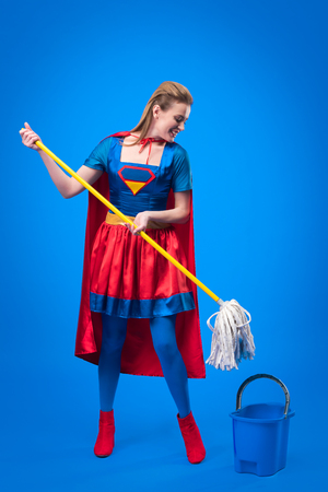 woman in superhero costume with mop and bucket for cleaning isolated on blue