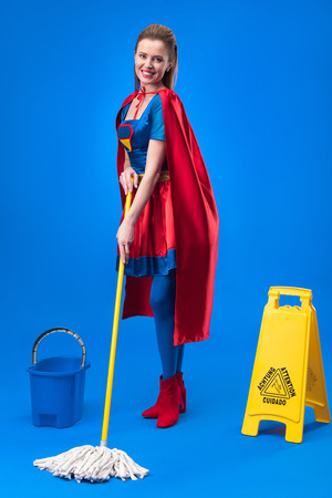 smiling woman in superhero costume with caution sign, bucket and mop for cleaning isolated on blue