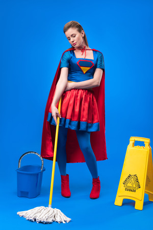 attractive woman in superhero costume with caution sign, bucket and mop for cleaning isolated on blue