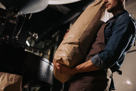 partial view of worker in apron holding paper bag of coffee beans in hands